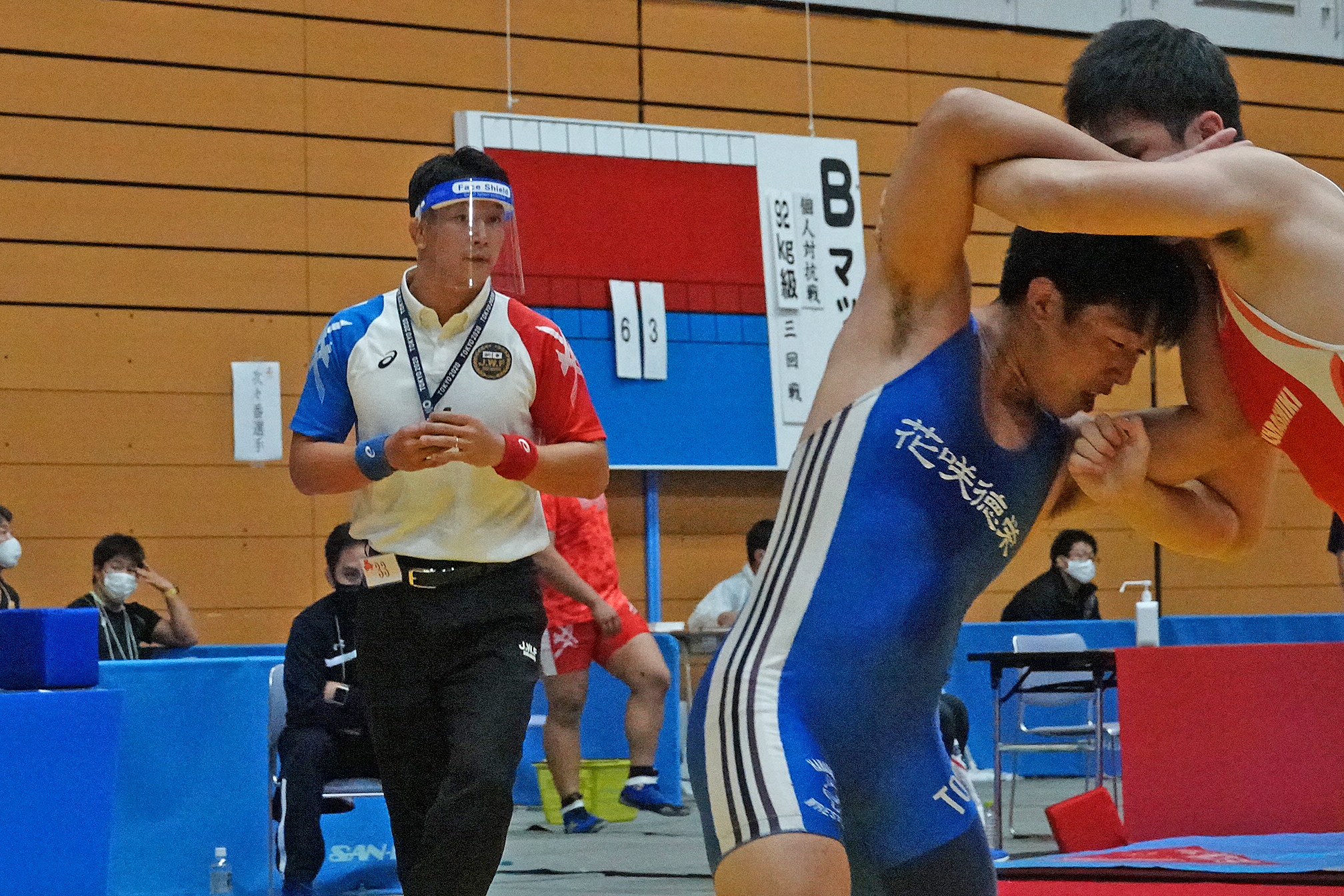 A referee wearing a face shield keeps an eye on the action. (Japan Wrestling Federation photo)